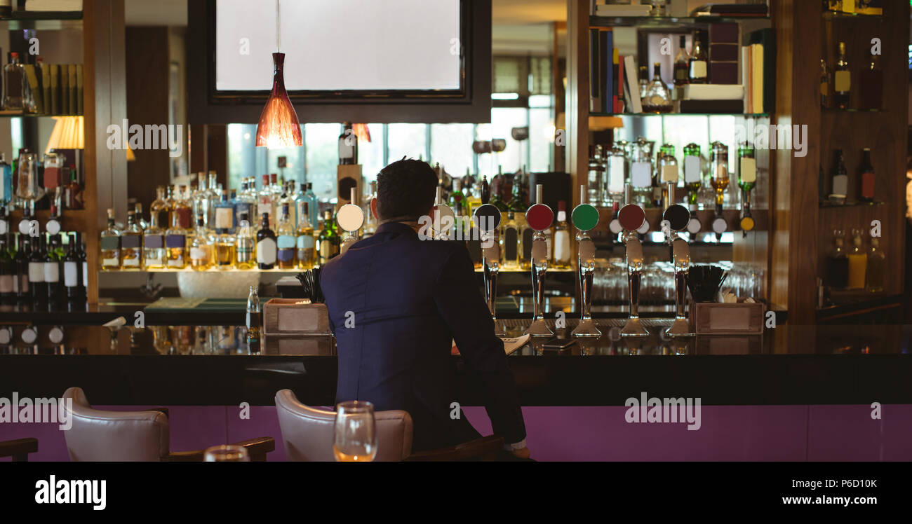 Businessman having a glass of whisky in hotel - Stock Image