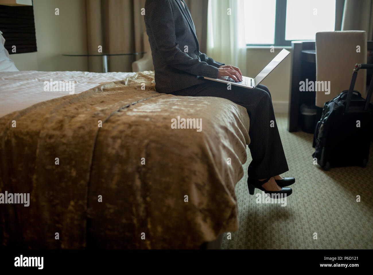 Businesswoman using laptop on bed - Stock Image