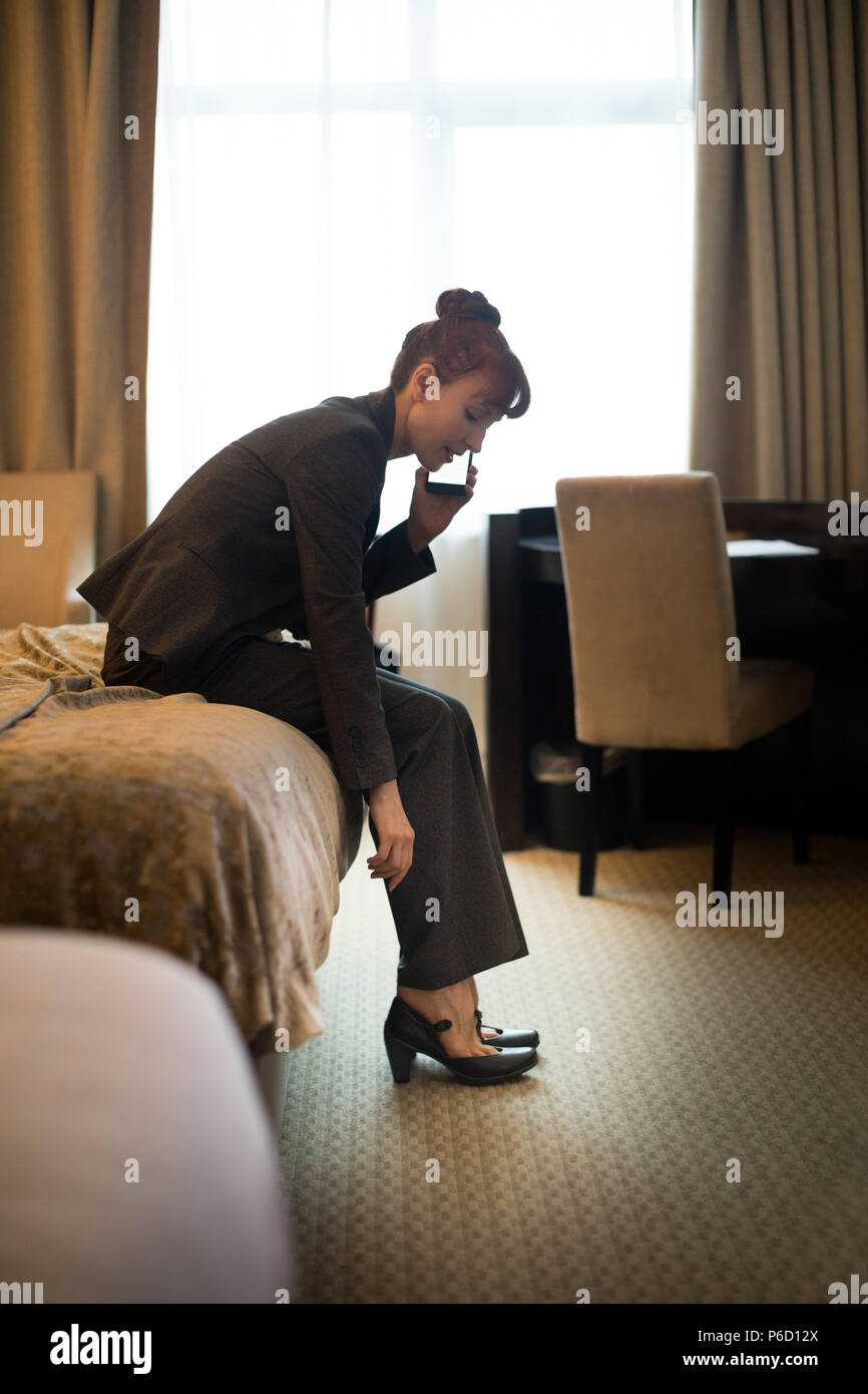 Businesswoman talking on mobile phone while wearing shoes - Stock Image