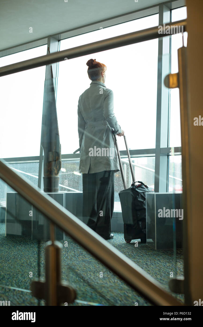 Businesswoman standing with luggage in hotel room - Stock Image