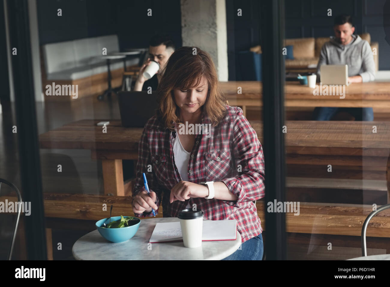 Businesswoman writing on a diary in cafeteria - Stock Image