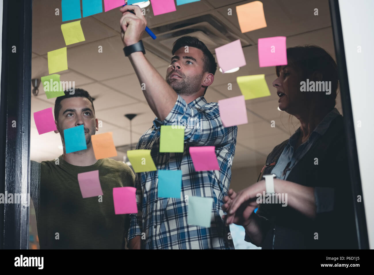 Business colleagues writing on sticky note - Stock Image