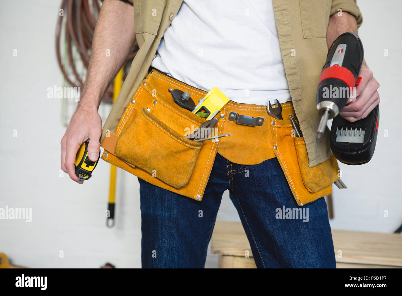 Male carpenter with tool belt in workshop - Stock Image