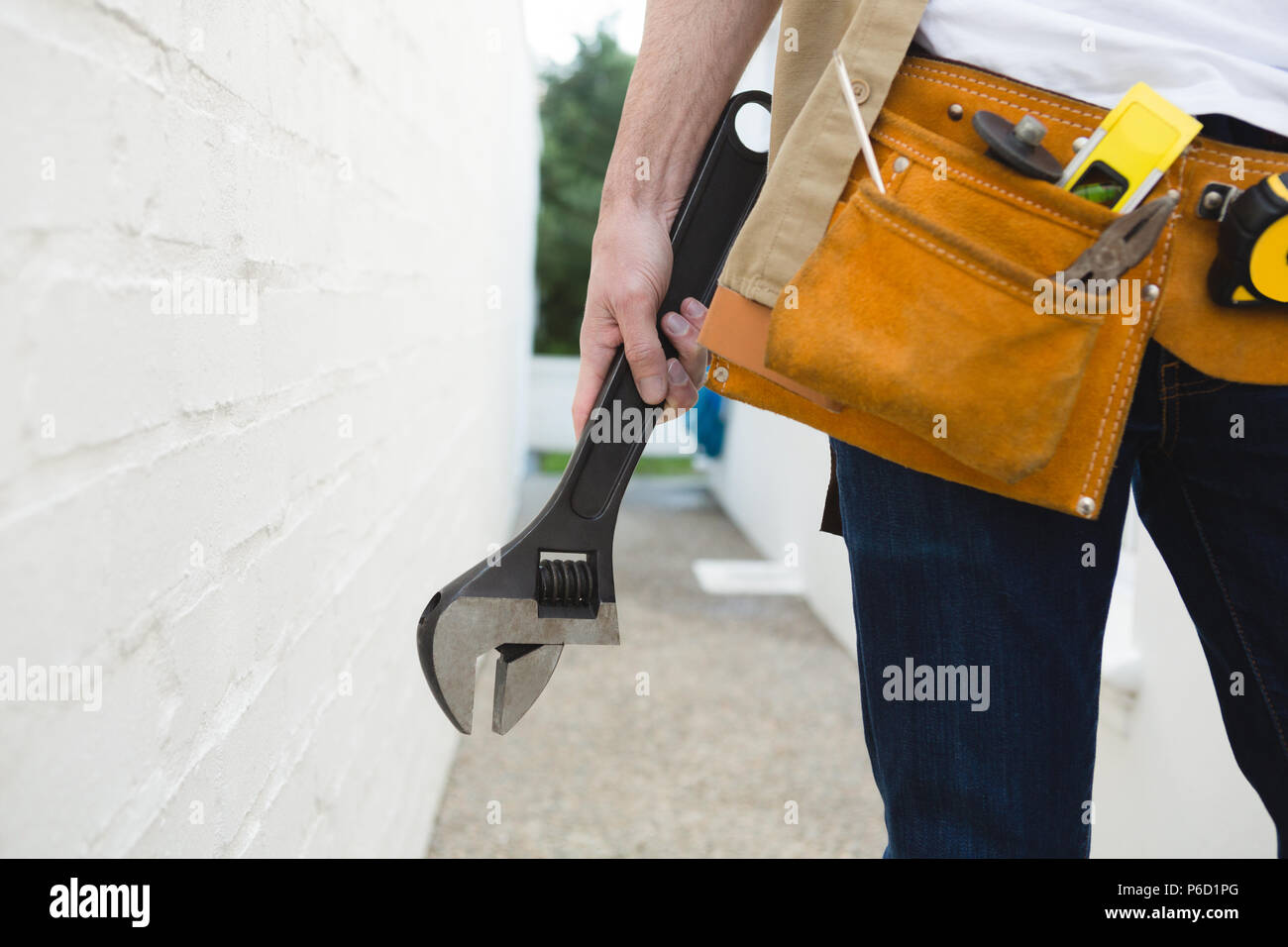 Male carpenter with tool belt holding wrench - Stock Image