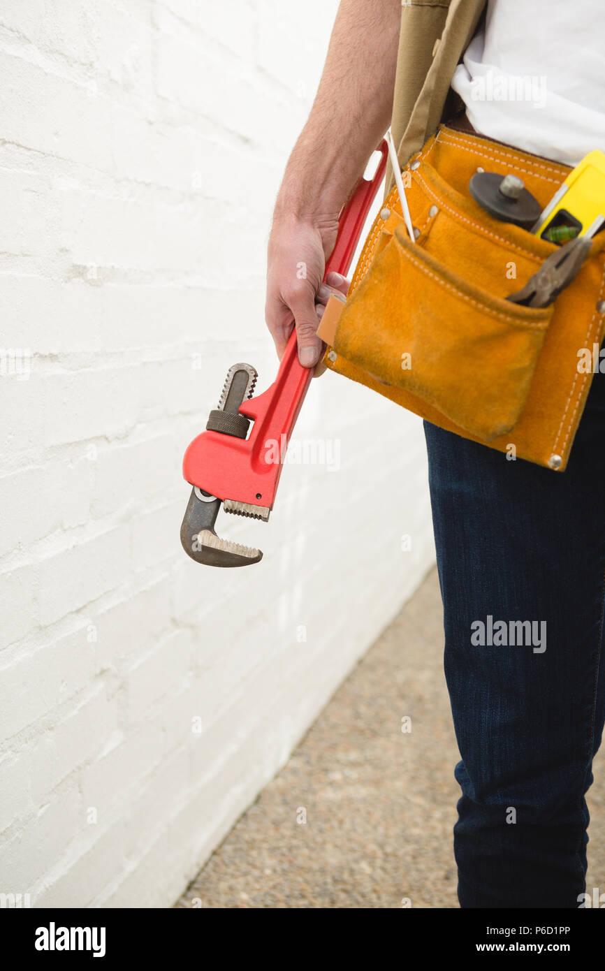 Male carpenter with tool belt holding clamp - Stock Image
