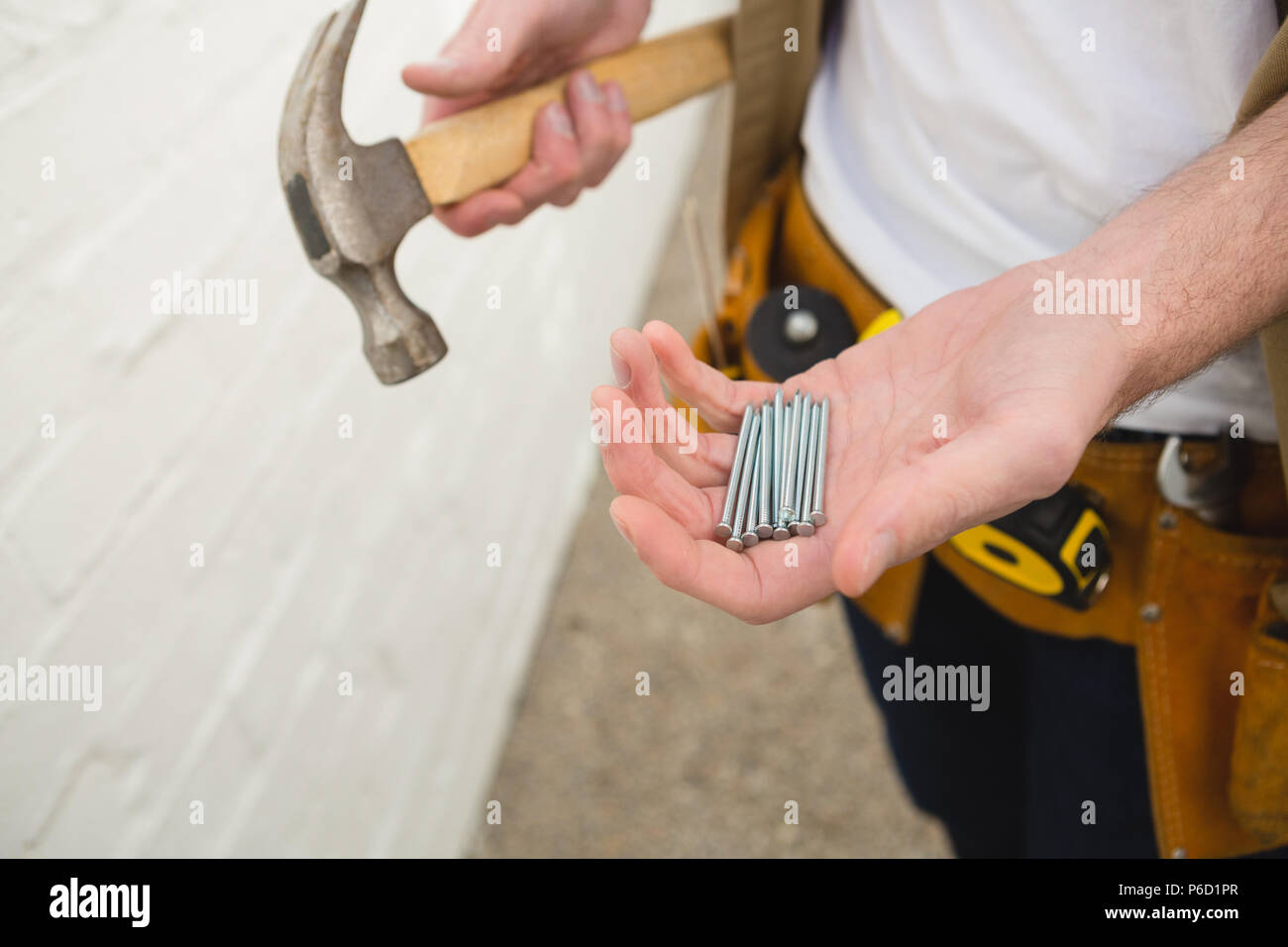 Male carpenter holding hammer and nails - Stock Image