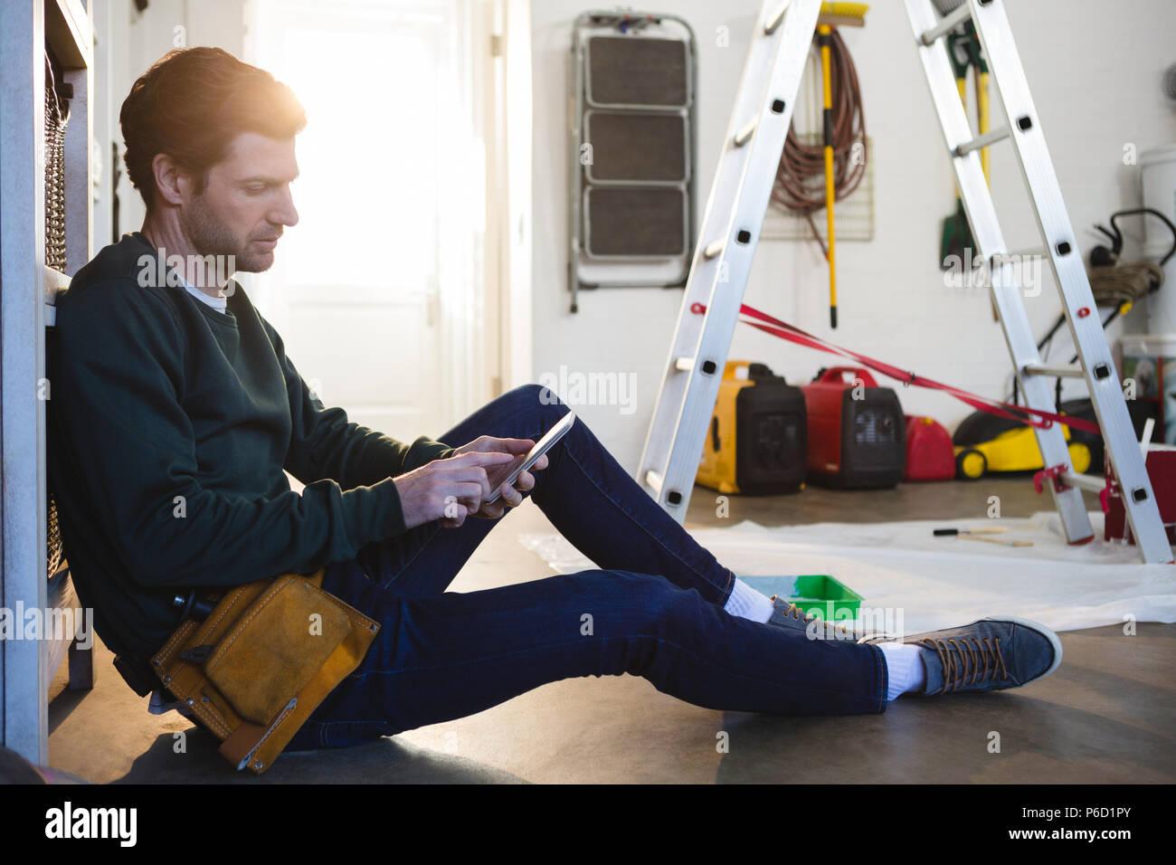 Male carpenter using mobile phone - Stock Image