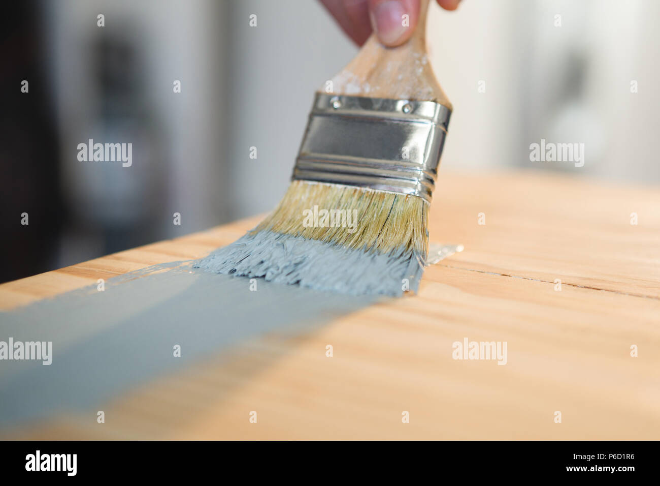Male carpenter painting a table - Stock Image