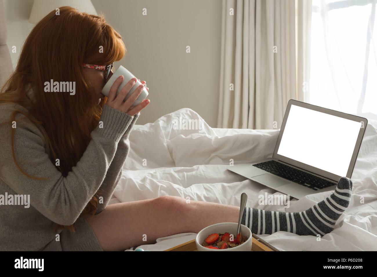 Woman having black coffee in bedroom Stock Photo