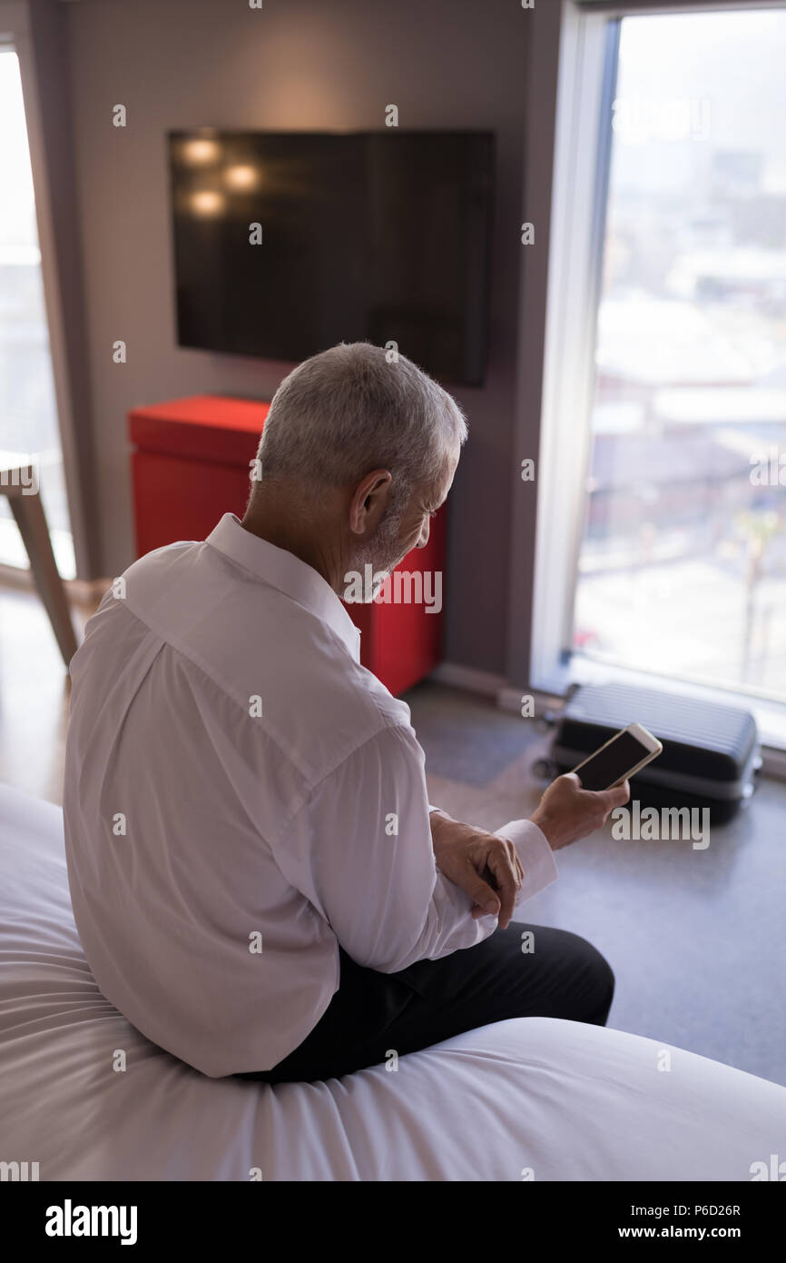 Businessman using a smart phone on bed - Stock Image