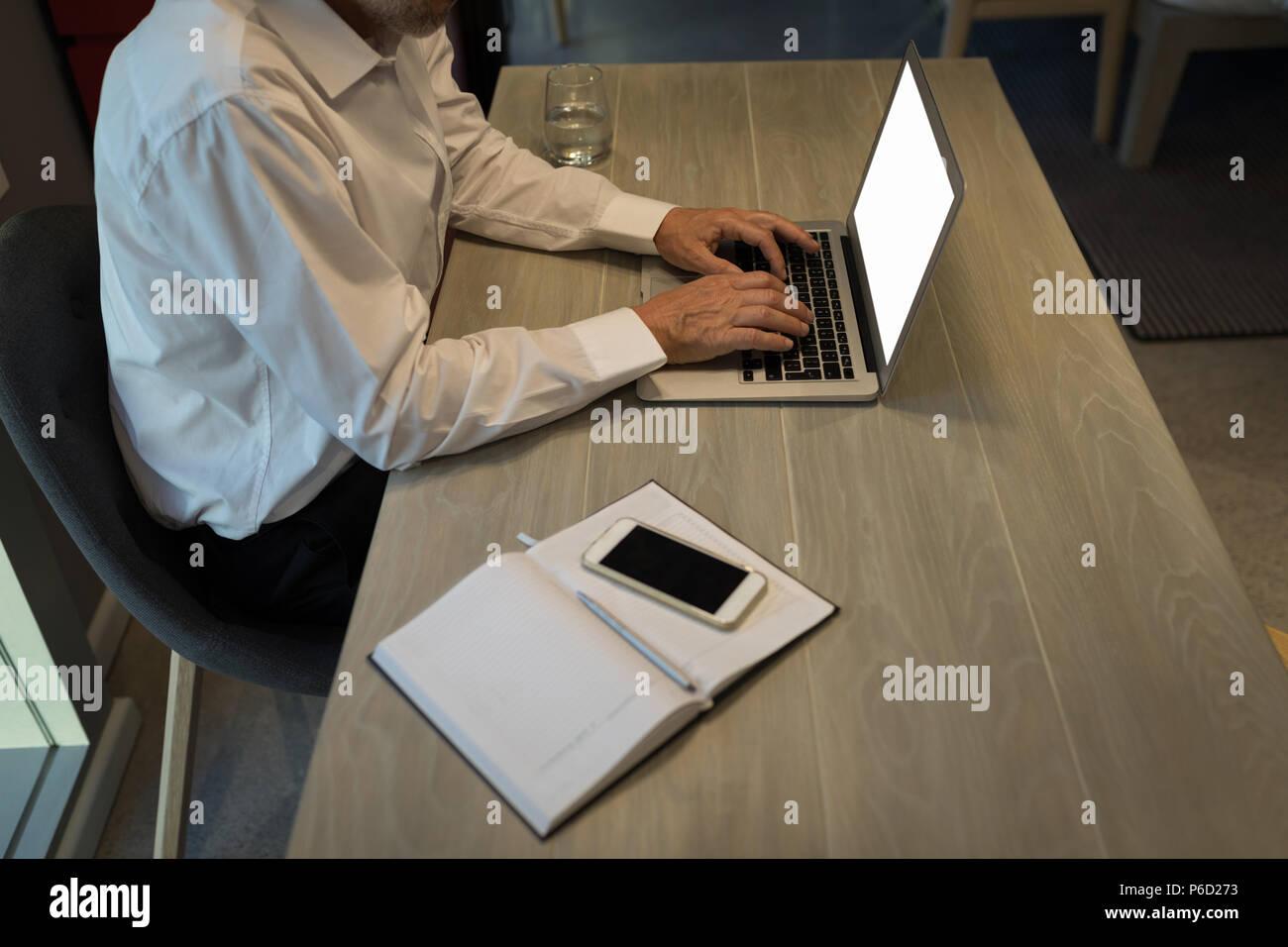 Businessman using a laptop at desk Stock Photo
