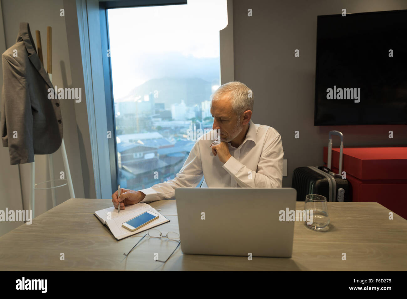 Businessman writing notes on diary at desk - Stock Image