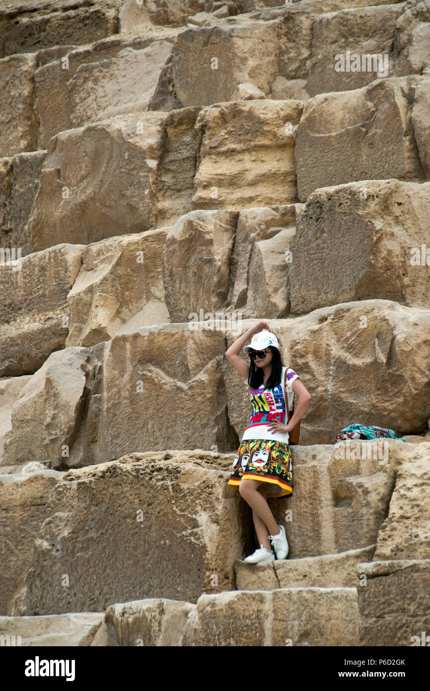Asian girl tourist poses for photos in front of the Great Pyramid of Giza (Pyramid of Khufu, Pyramid of Cheops) at Giza, Egypt. Stock Photo