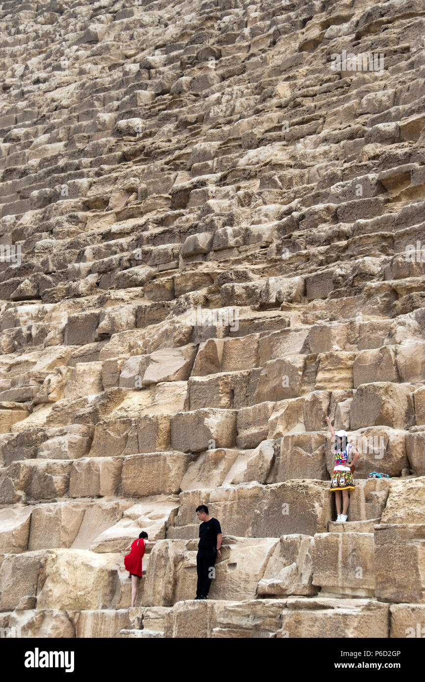 Asian tourists pose for photos in front of the Great Pyramid of Giza (Pyramid of Khufu, Pyramid of Cheops) at Giza, Egypt. Stock Photo