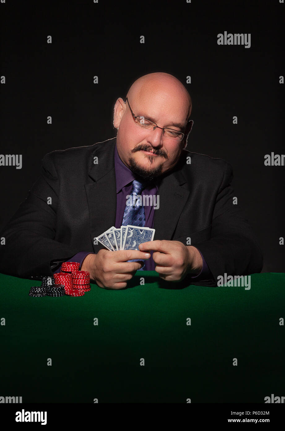 card player in business suit.  Glasses and necktie with gaming chips against black background. - Stock Image