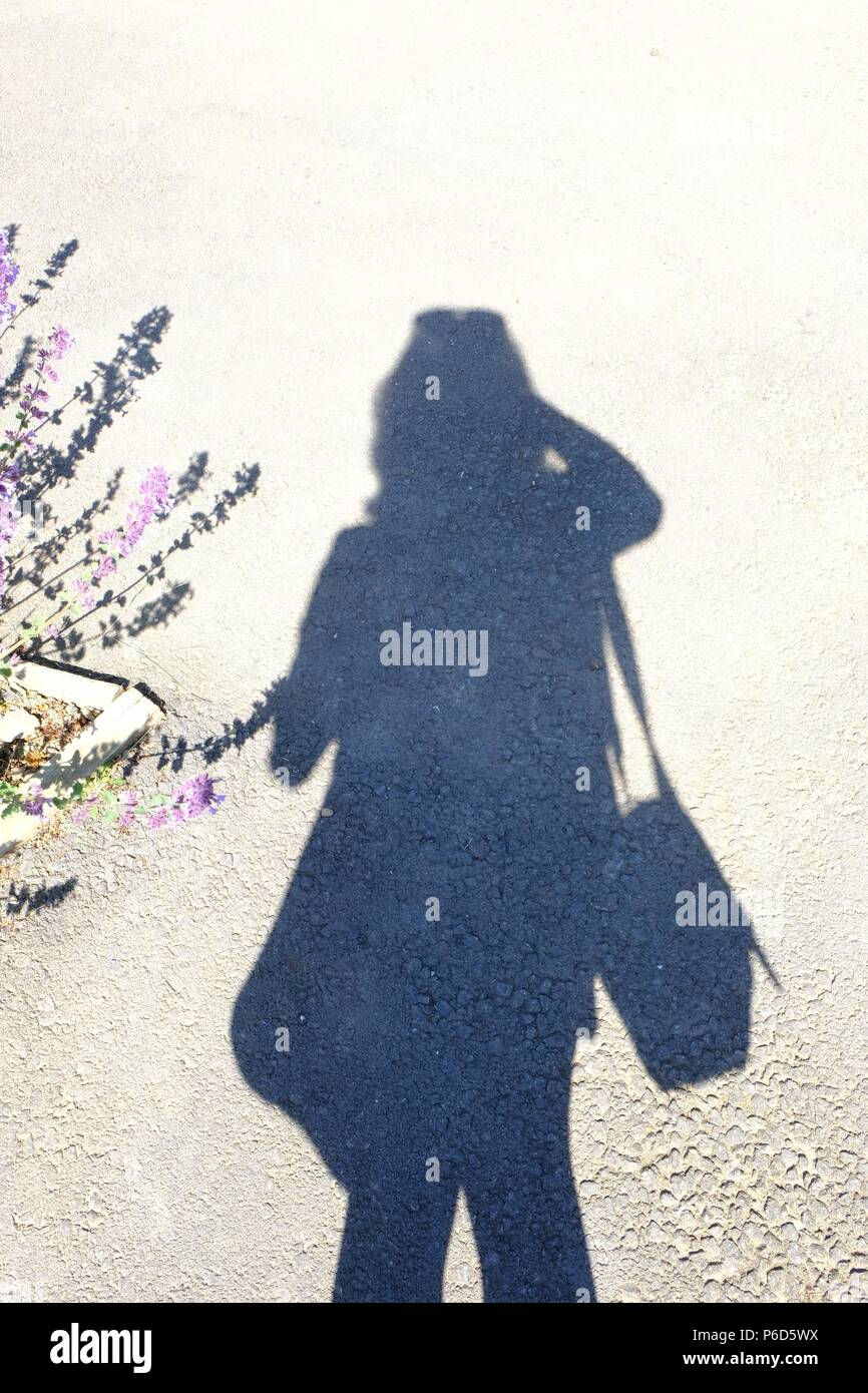 Shadow of a girl taking a picture of herself (self portrait) - Stock Image