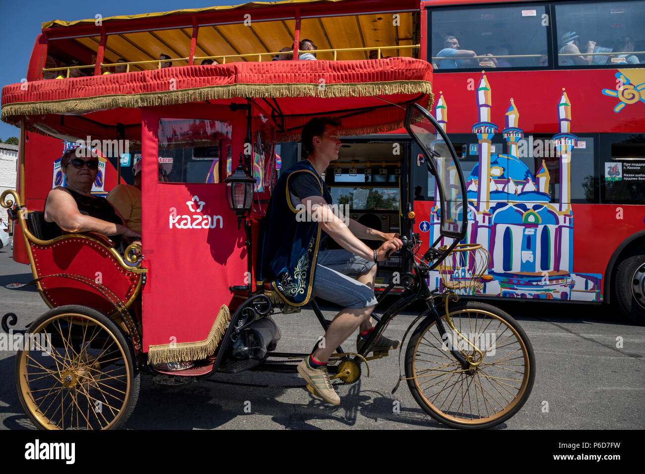 Trishaw gets tourists on bakground of the sightseeing bus near the Kremlin in Kazan city, the Republic of Tatarstan, Russia - Stock Image