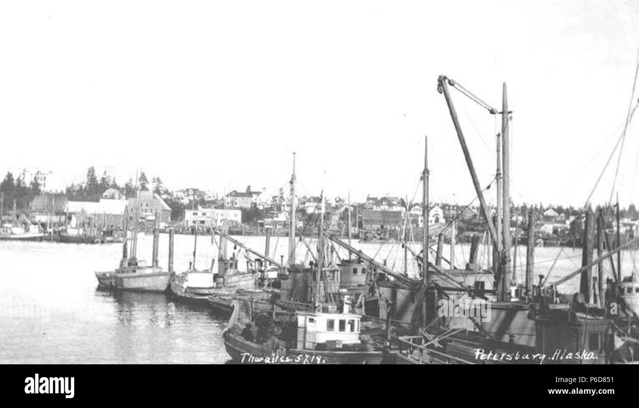 . English: Waterfront and fishing boats, Petersburg, ca. 1912 . English: Caption on image: Petersburg, Alaska PH Coll 247.840 Petersburg is located on the north end of Mitkof Island, where the Wrangell Narrows meet Frederick Sound. It lies midway between Juneau and Ketchikan, about 120 miles from either community. Tlingit Indians from Kake utilized the north end of Mitkof Island as a summer fish camp. Some reportedly began living year-round at the site, including John Lot. Petersburg was named after Peter Buschmann, a Norwegian immigrant and a pioneer in the cannery business, who arrived in th - Stock Image