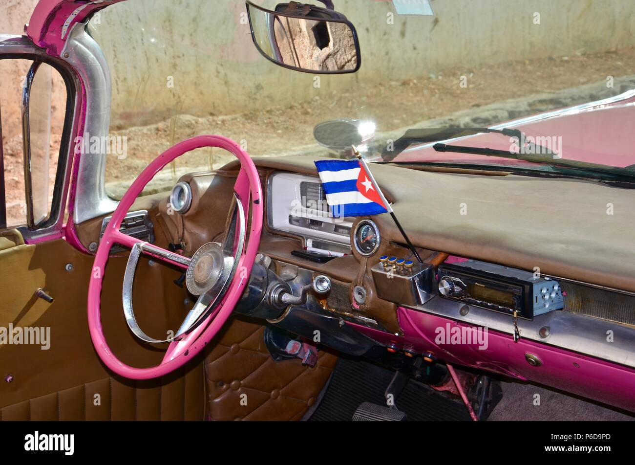 Interieur of a pink vintage car in Havana, Cuba, old, flag, street, traffic, taxi, tourism, caribbean, american, vehicle, mirror, pink steering wheel - Stock Image