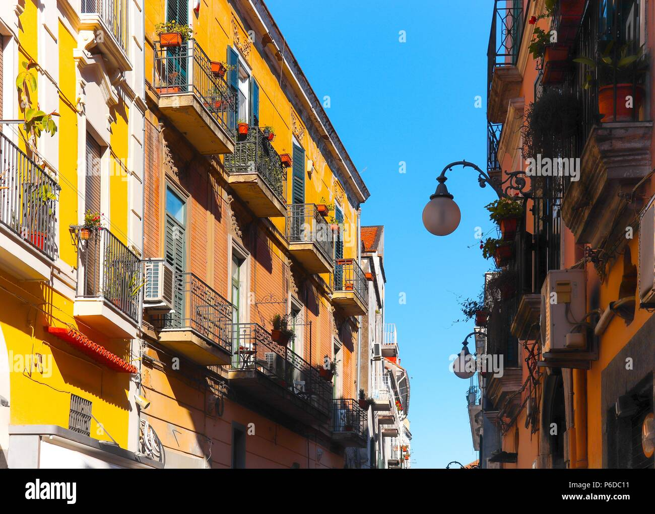 Italian narrow street with colorful houses, street light and blue sky between on sunny summer day. Vietri sul Mare, South of Italy Stock Photo