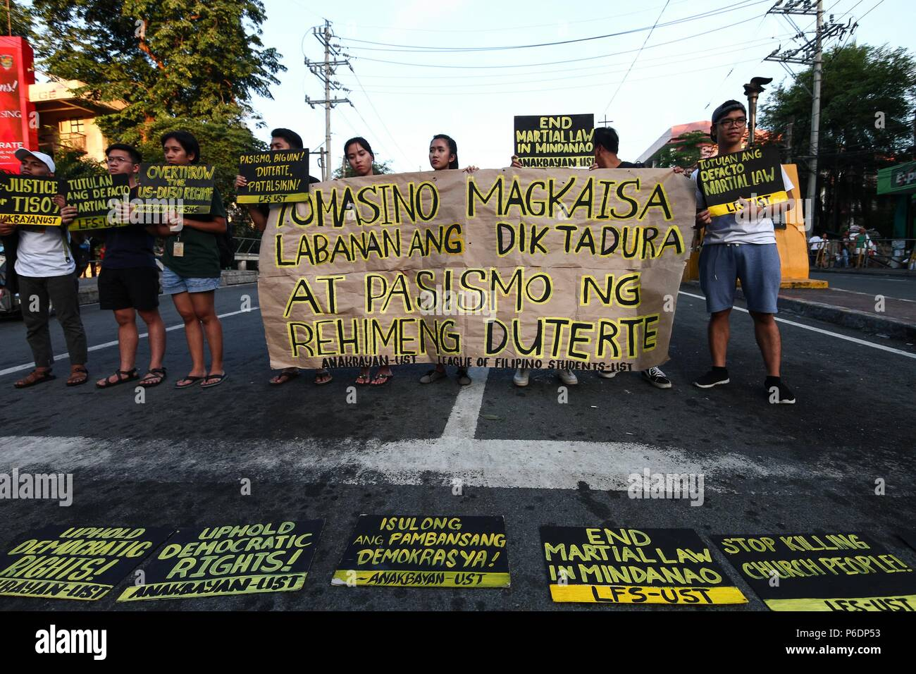 Students holding placards and a banner during the protest. Students from the University of Santo Thomas staged a lightning rally near the presidential palace in Mendiola, Friday afternoon, against the recent deaths of Catholic priests. It was Part of the nationwide Black Friday protests, the students called for justice for Tisoy Argoncillo's death while in police detention for loitering. The group also called for the end of the Martial Law in Mindanao. - Stock Image