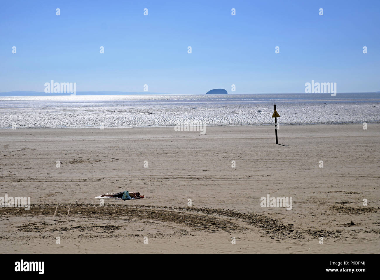 Weston-super-Mare, UK. 29th June, 2018. UK weather: as the heatwave continues and the temperature exceeds 80º F, a sunbather relaxes on the beach. Keith Ramsey/Alamy Live News - Stock Image