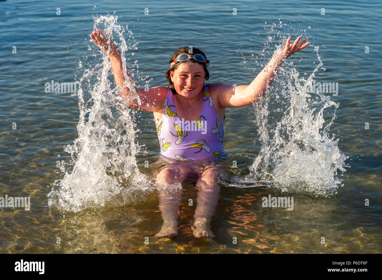 Bantry, West Cork, Ireland. 29th June, 2018. After a scorchingly hot day, 11 year old Nora Fox from Bantry plays in the water as the sun goes down in Bantry. The rest of the weekend will be cooler than previous days with rain forecast for next week. Credit: Andy Gibson/Alamy Live News. - Stock Image