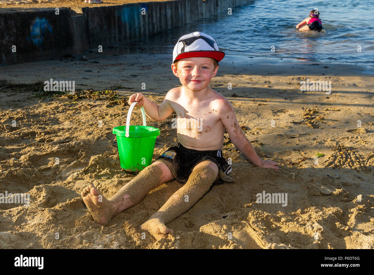Bantry, West Cork, Ireland. 29th June, 2018. After a scorchingly hot day, 5 year old Kasper Keane from Bantry plays on the beach as the sun goes down in Bantry. The rest of the weekend will be cooler than previous days with rain forecast for next week. Credit: Andy Gibson/Alamy Live News. - Stock Image