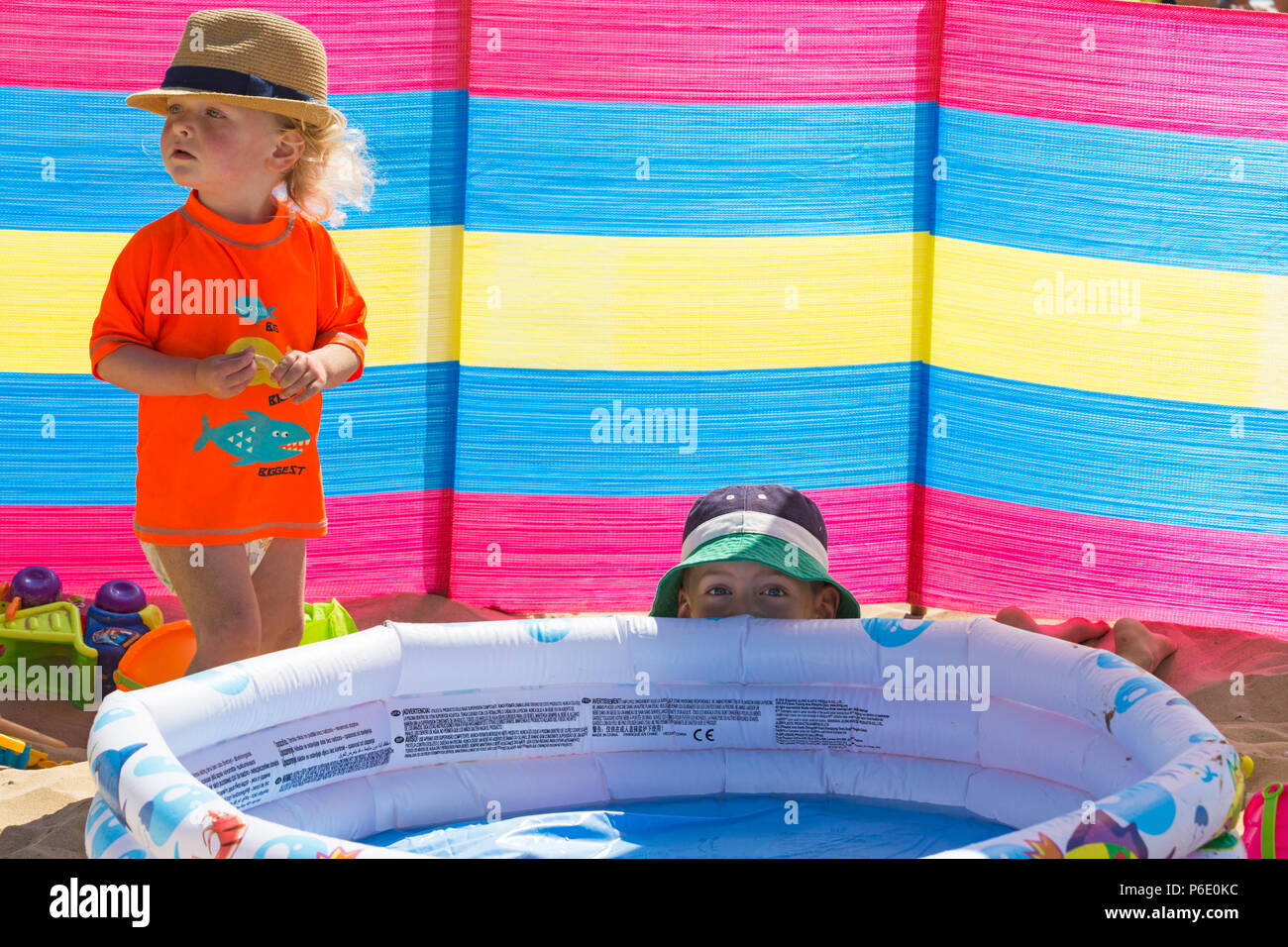 Bournemouth, Dorset, UK. 30th June 2018. UK weather: the heatwave continues and another hot sunny day at Bournemouth beaches. Mid morning and the beaches are getting packed and car parks full as sunseekers head to the seaside. A slight breeze makes the heat more bearable. Six and two year old boys wait patiently for dad to fill the paddling pool! Credit: Carolyn Jenkins/Alamy Live News - Stock Image