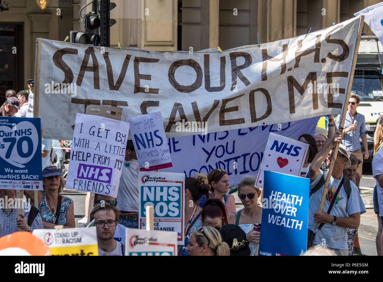 London, UK. 30 June, 2018. A large banner amongst the placards reads ' Save our NHS, It saved me'. With the NHS 70 years old this year, thousands marched through central London in a National rally to show support for the service and to demand more funding from the Government. David Rowe/Alamy Live News - Stock Image