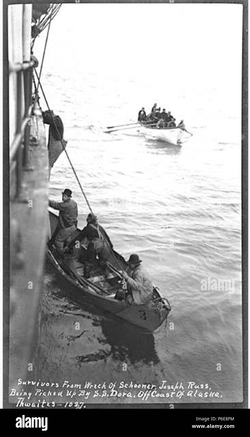 . English: Survivors from wreck of schooner JOSEPH RUSS boarding steamer DORA, off Chirikof Island, April 1912 . English: Caption on image: Survivors from wreck of schooner, Joseph Russ, being picked up by SS Dora off coast of Alaska PH Coll 247.290 The codfishing schooner JOSEPH RUSS struck the rocks off Chirikof Island on April 21 and was totally demolished, First Mate J. Jorgensen being drowned. Capt. Charles Foss and the remaining 29 men of the crew reached the island where they were in danger of death through cold and starvation. Second Mate A.E. Reeve and five volunteers put out in two s - Stock Image
