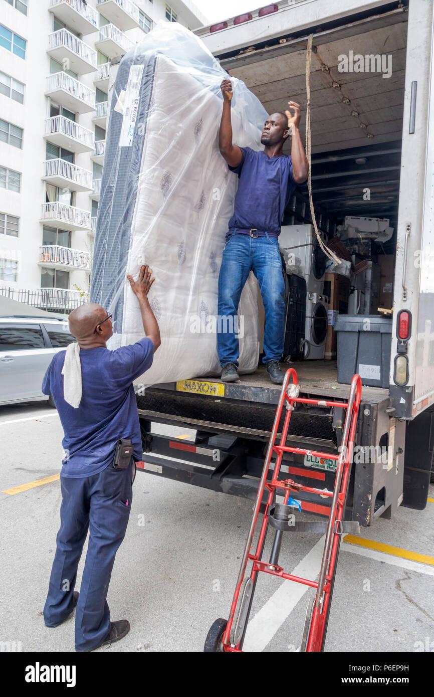 Miami Beach Florida mattress delivery truck Black man delivering unloading dolly manual labor - Stock Image