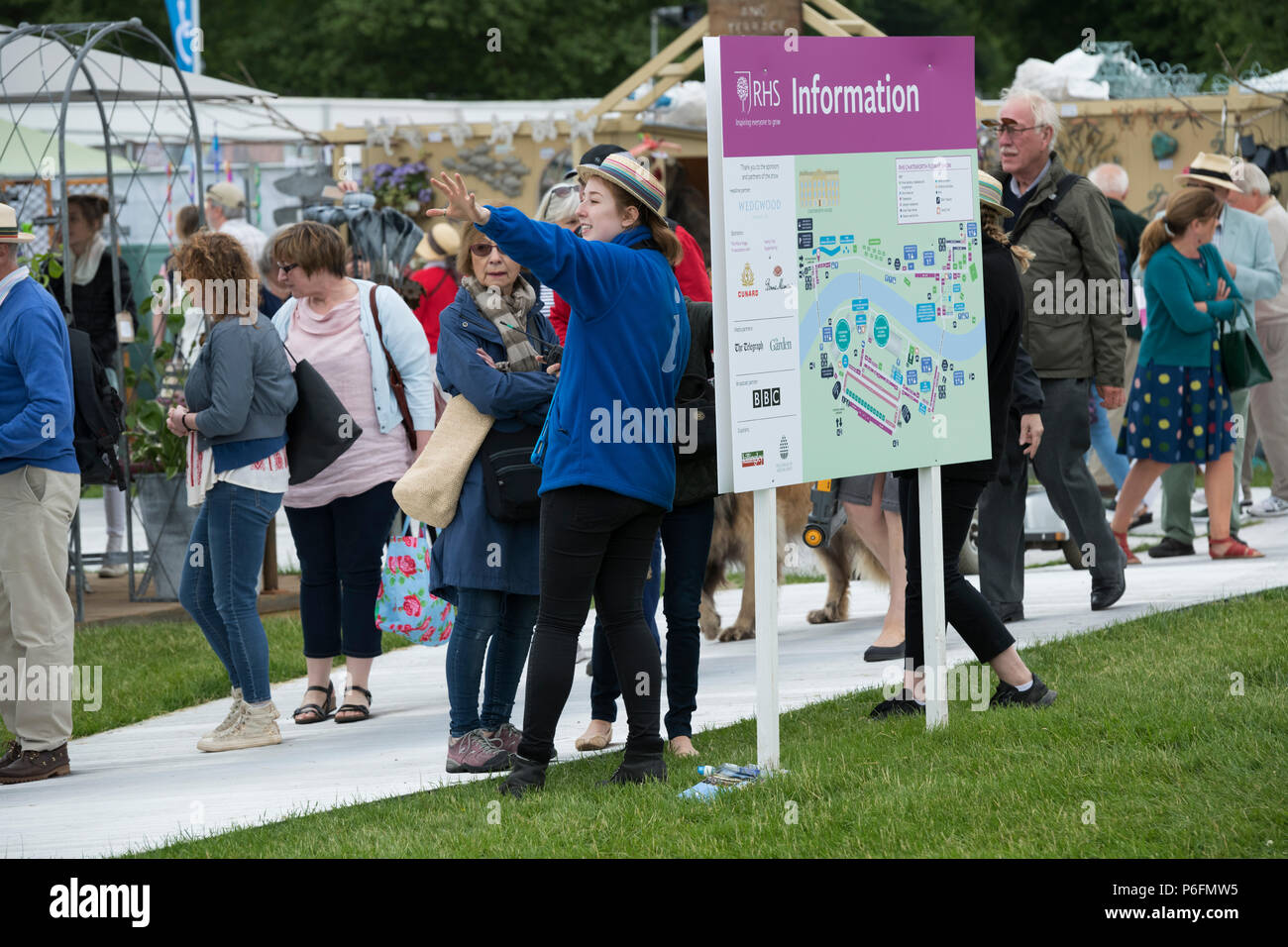 RHS volunteer working by large information board map, pointing, directing & guiding female showground visitor - Chatsworth Flower Show, Derbyshire, UK - Stock Image