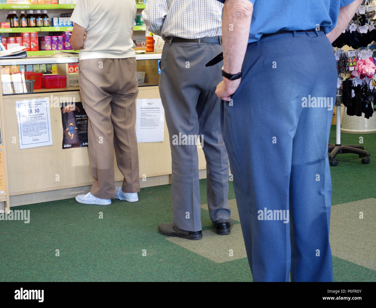 people in a queue at a local chemist pharmacy shop Stock Photo
