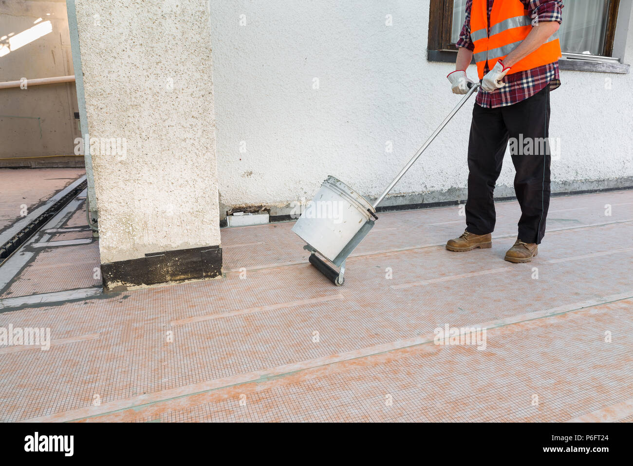 Waterproofing and thermal insulation of a terrace - roof. A professional worker is installing a sheet - applied polyethylene waterproofing membrane - Stock Image