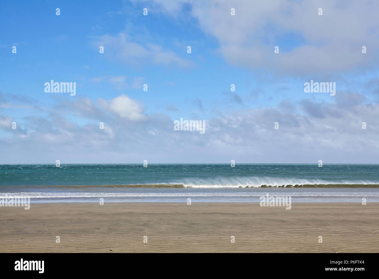 View from a beach on the west coast of New Zealand looking out to the Tazman Sea as a wave breaks on to the shore - Stock Image