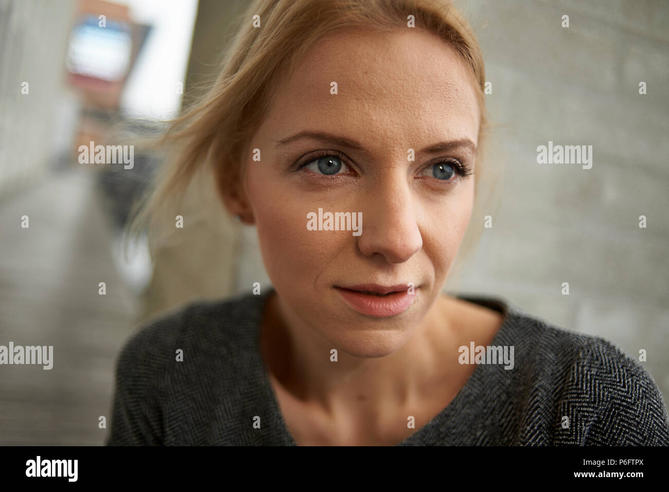 Close up of a young caucasian woman looking anxious and curious as if she is running away from something or someone - Stock Image