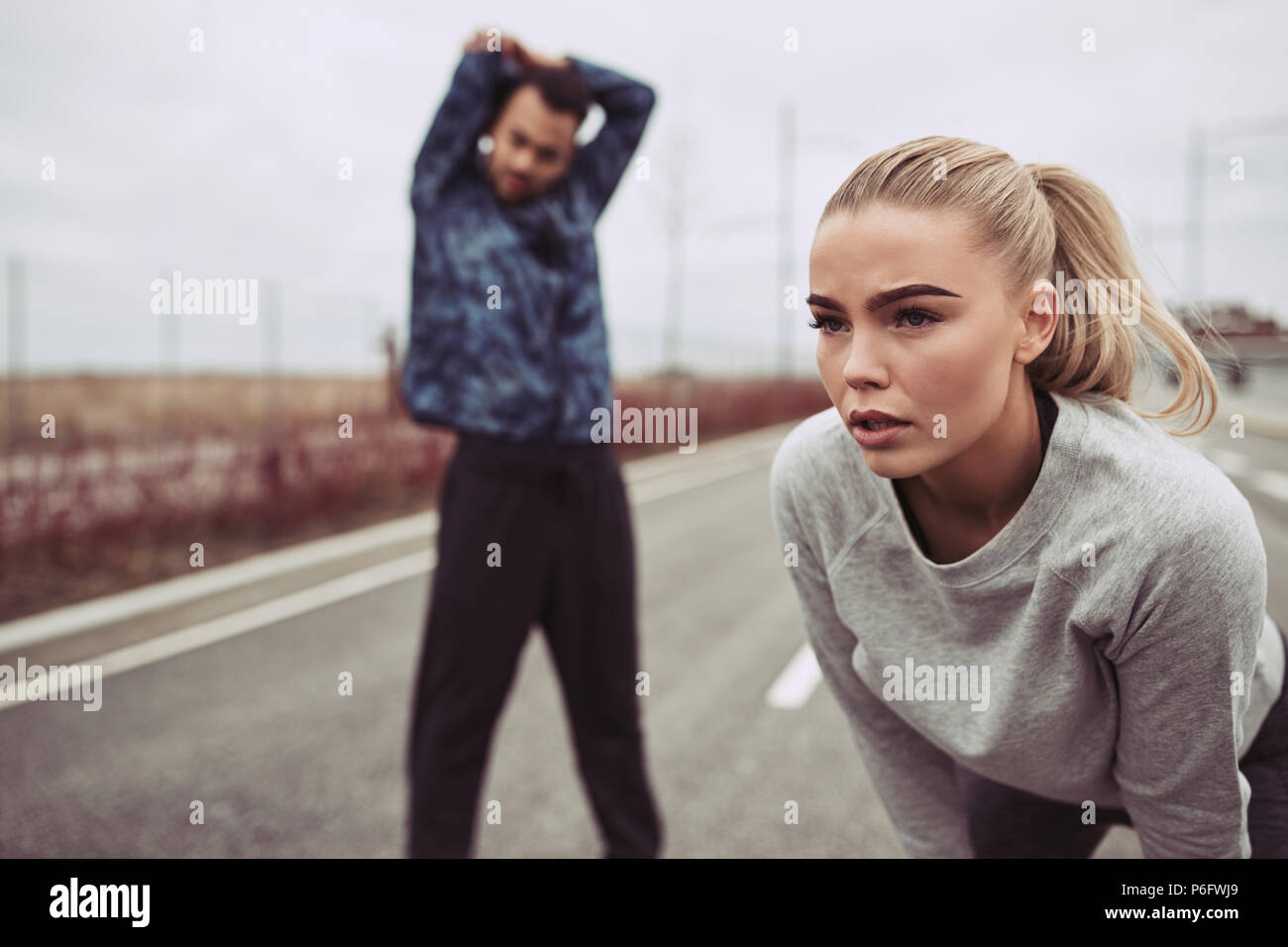 Yougn woman in sportswear preparing for a run along a country road with her boyfriend doing stretches in the background Stock Photo