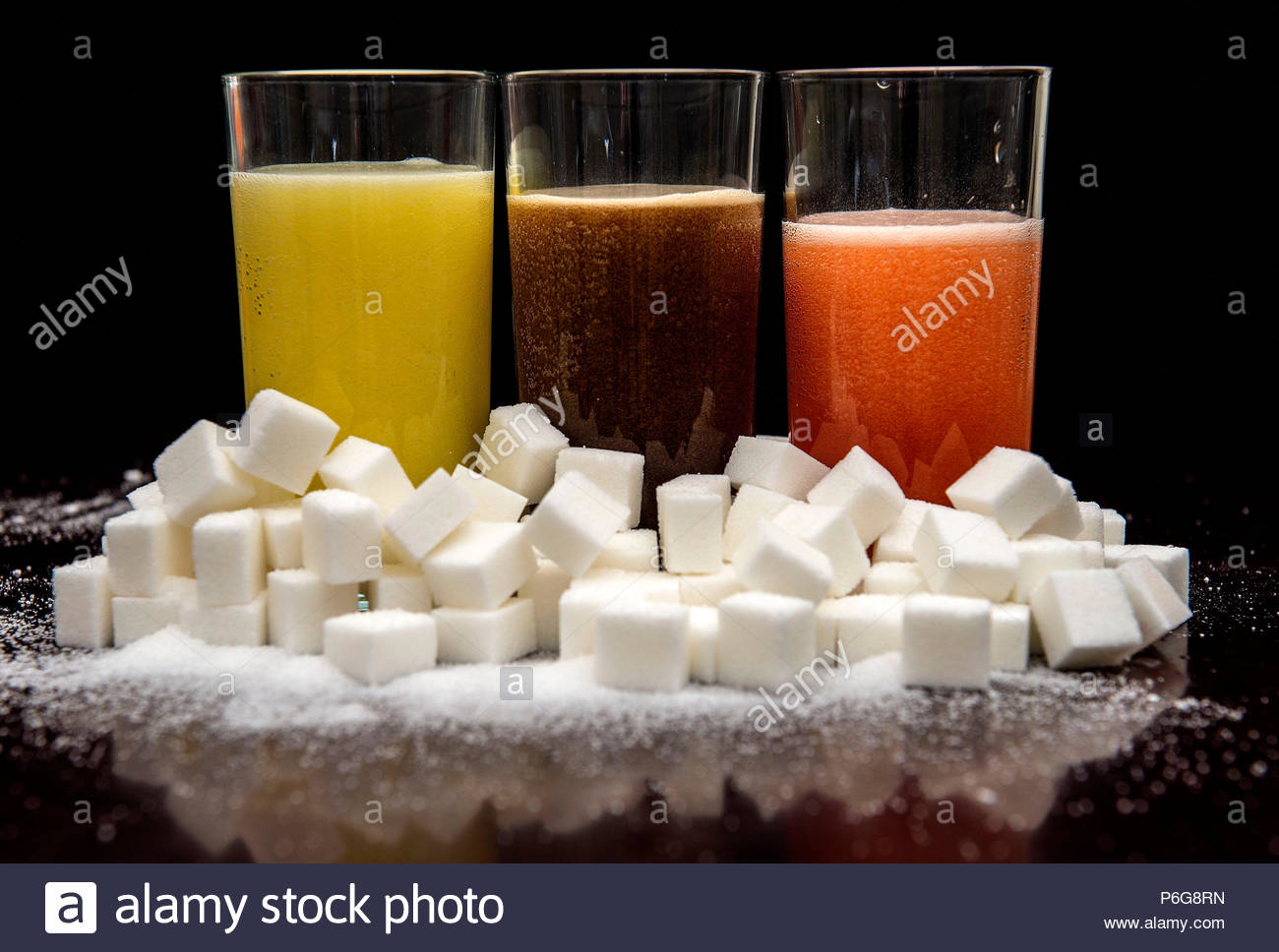 File photo dated 15/12/17 of soft drinks surrounded by sugar cubes. Ten million teaspoons of sugar have been removed from NHS canteens, shops and vending machines - the equivalent of 1.1 million cans of fizzy drink - after the majority of hospital trusts signed up to a voluntary scheme. Stock Photo