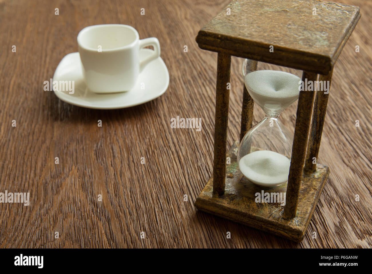 Hourglass on the Oak table as time passing concept for business deadline, urgency and running out of time. - Stock Image