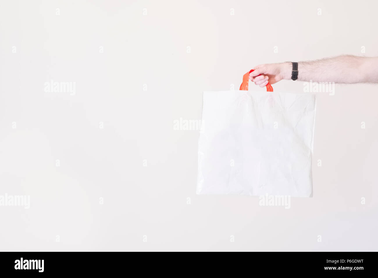 Blank plastic bag white background arm stretch out holding recycle plastic non biodegradable - Stock Image