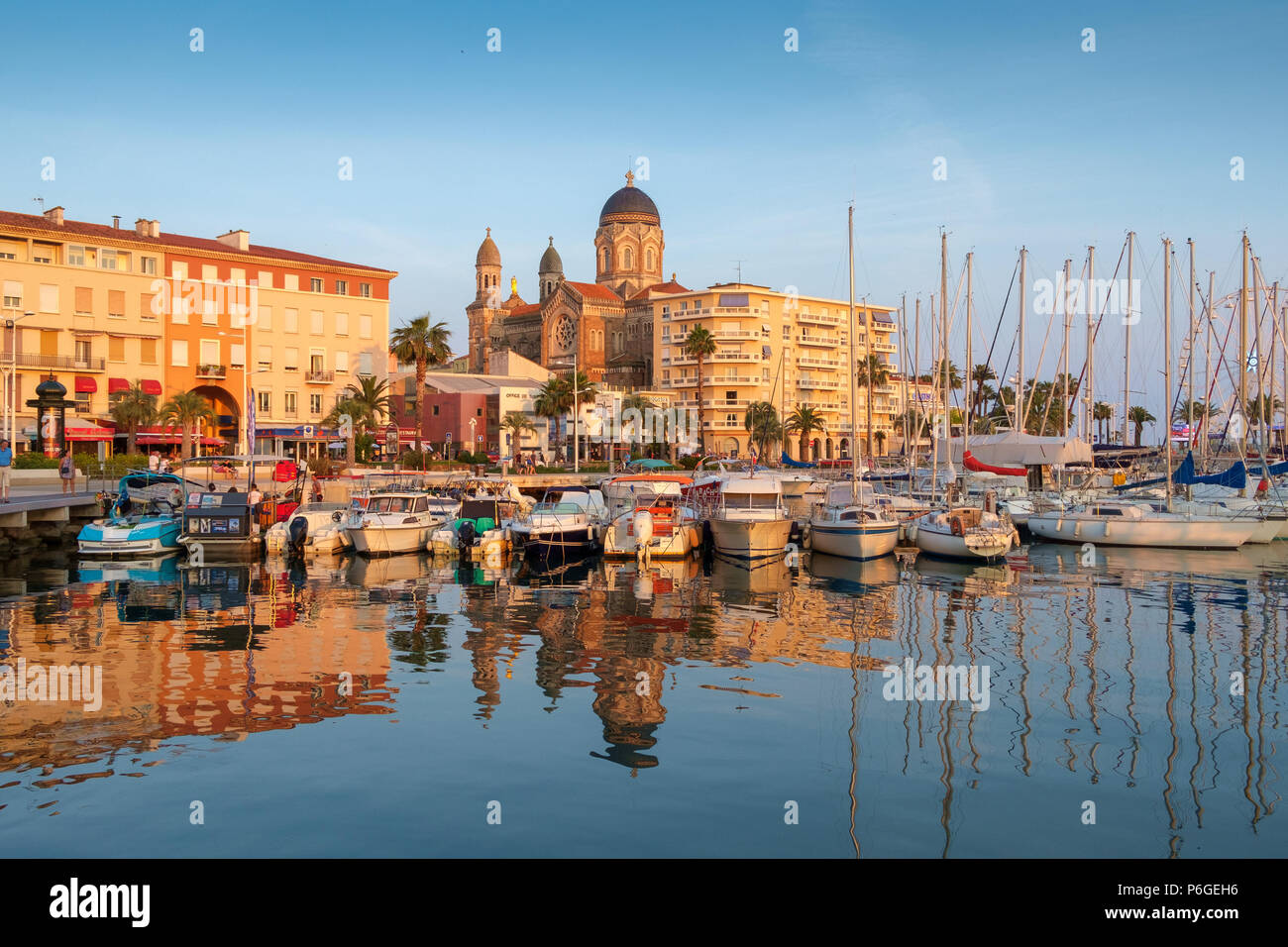 The evening sun shines on the cathedral, seafront buidings and boats, Saint Raphael, France. - Stock Image
