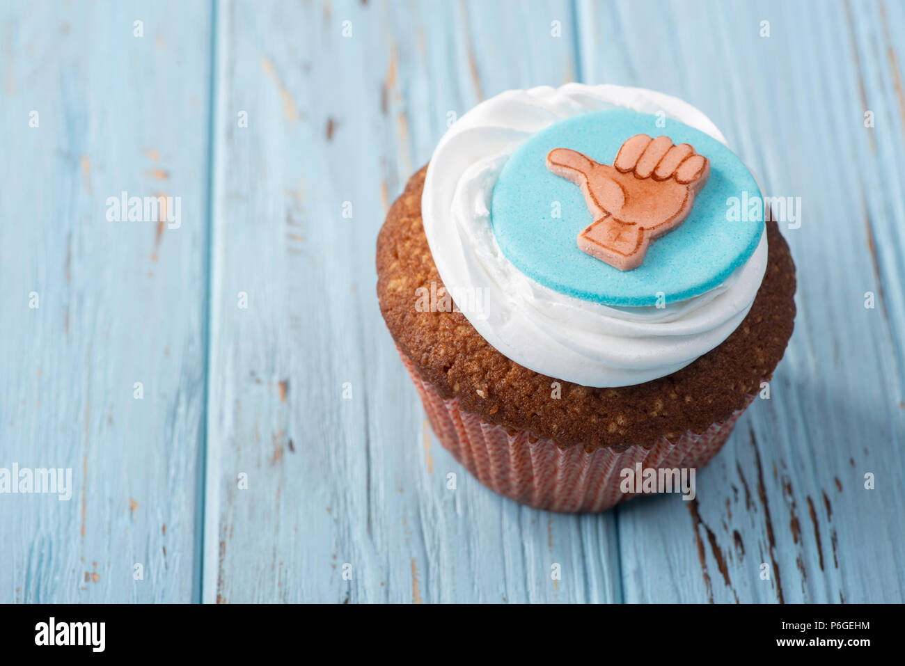 Tasty cake on blue wooden table, thumb up Stock Photo