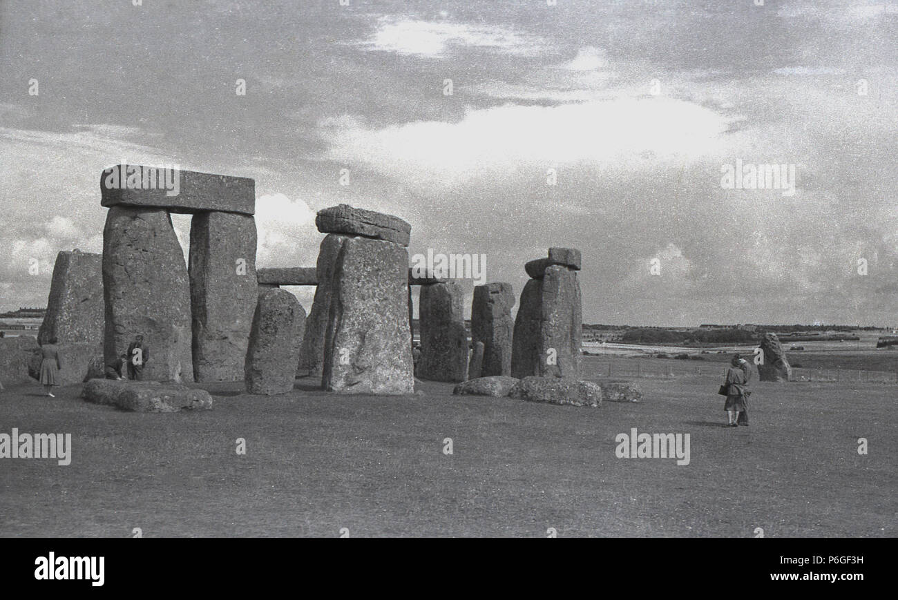 1950s, historical picture of visitors at Stonehenge, Wiltshire, England, the world famous prehistoric momument. In this era visitors to the ancient ring of standing stones could walk among them quite freely, but this was stopped in 1977 as a result of 'erosion' and now it is something that is only allowed on so-called 'special access visits'. - Stock Image