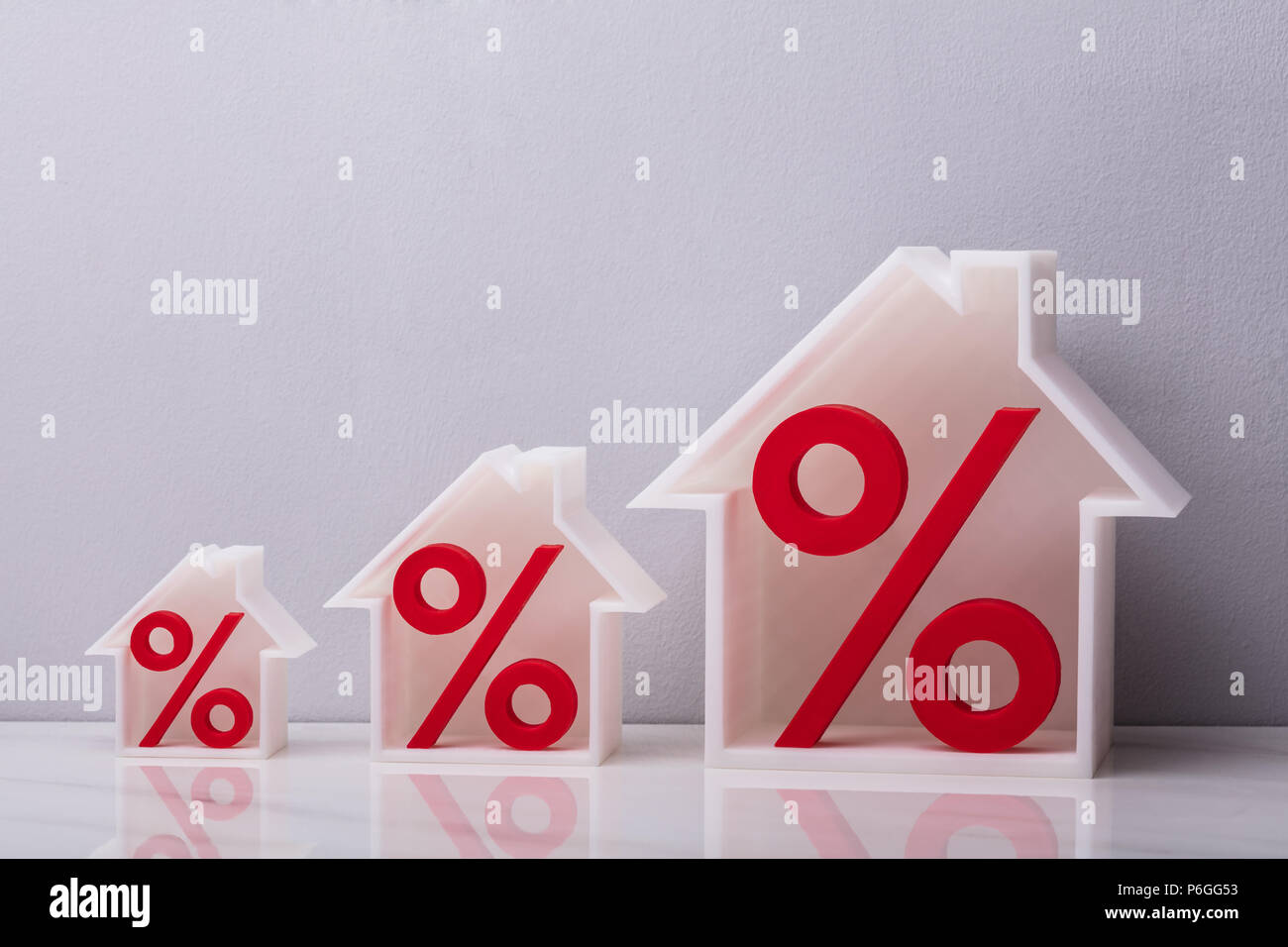 Percentage Symbols Inside Increasing House Models Against White Background - Stock Image