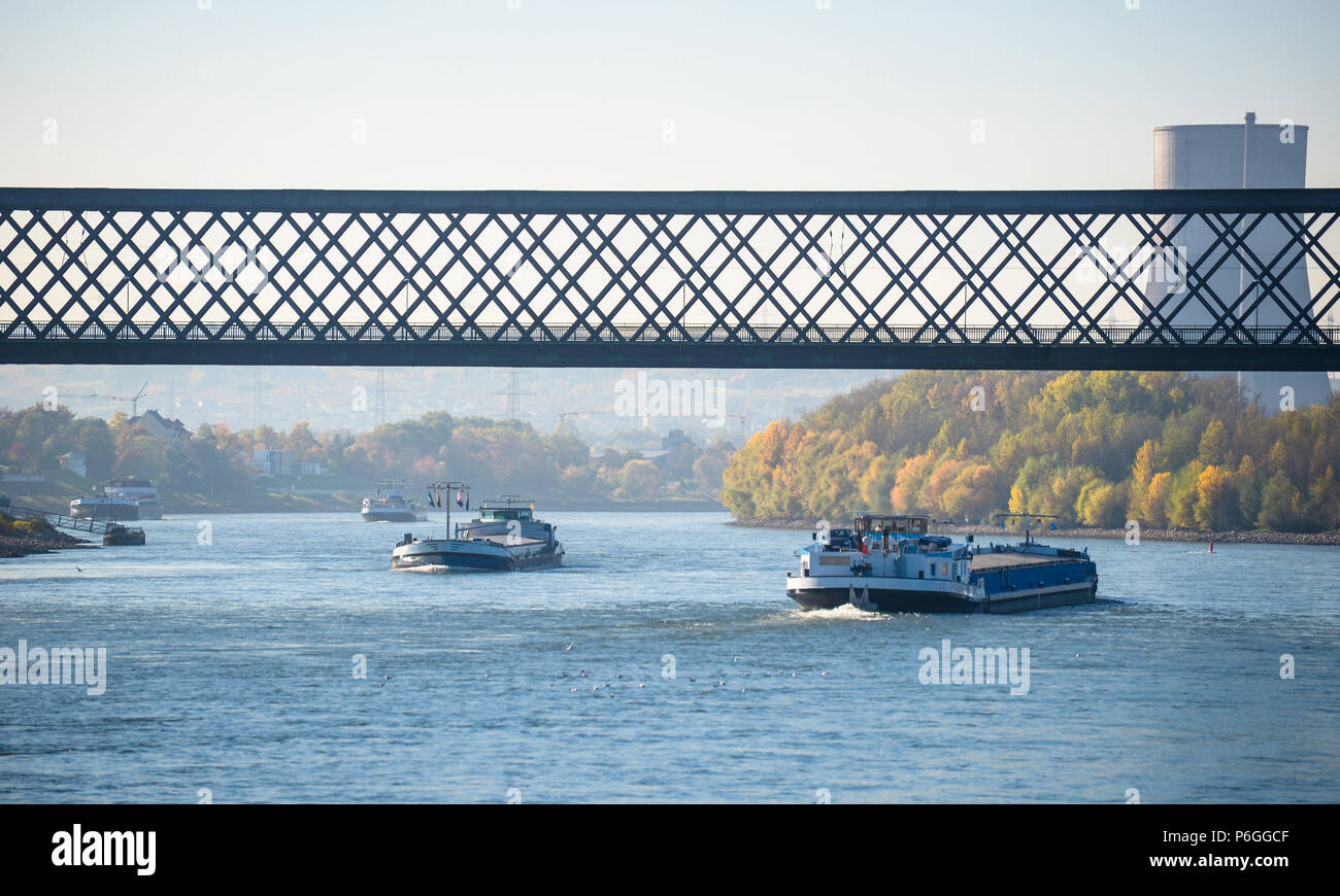 Sunny autumn day in Germany on the river Rhine. The barge flows under the railway bridge. A visible chimney of a nuclear power plant. Stock Photo