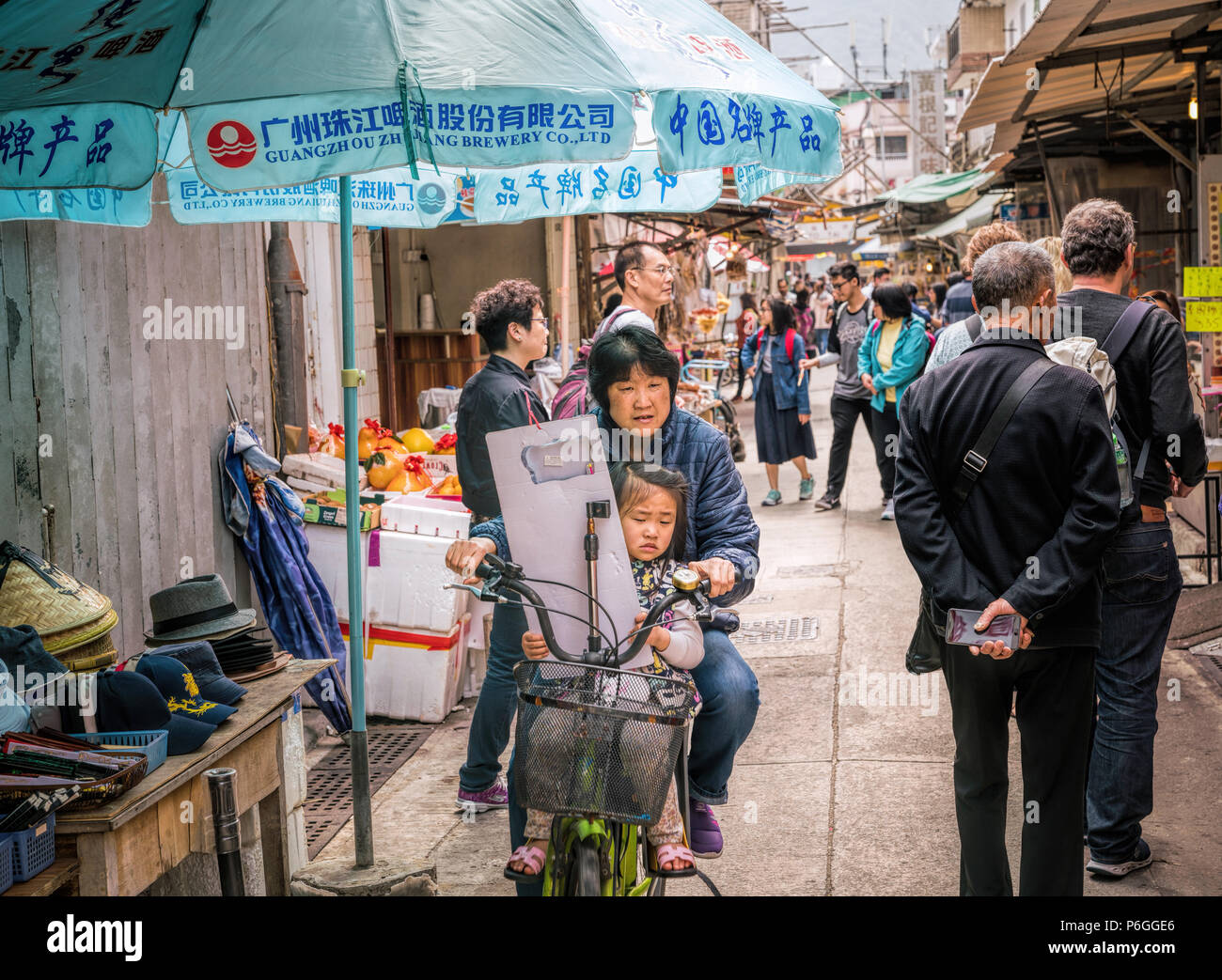 19 February 2018 - Lantau Island, Hong Kong. Asian woman cycling in the village street of Tai O with child on the bike. - Stock Image