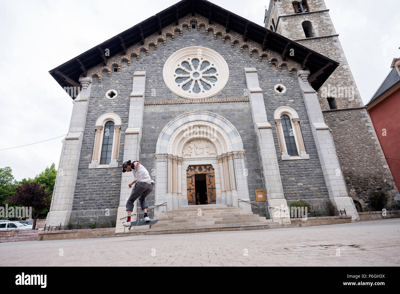 boy stunts on skate board in front of catholic church in barcelonette - Stock Image