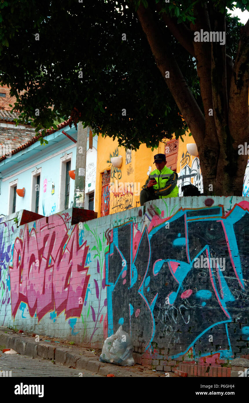 Security on the edge of La Candelaria, Bogota, looking at his mobile phone. - Stock Image