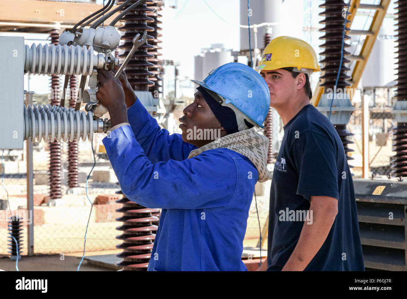 Johannesburg, South Africa, 04/11/2012, Electricians working on high voltage power lines. Highly skilled workmen servicing the electricity gri Stock Photo